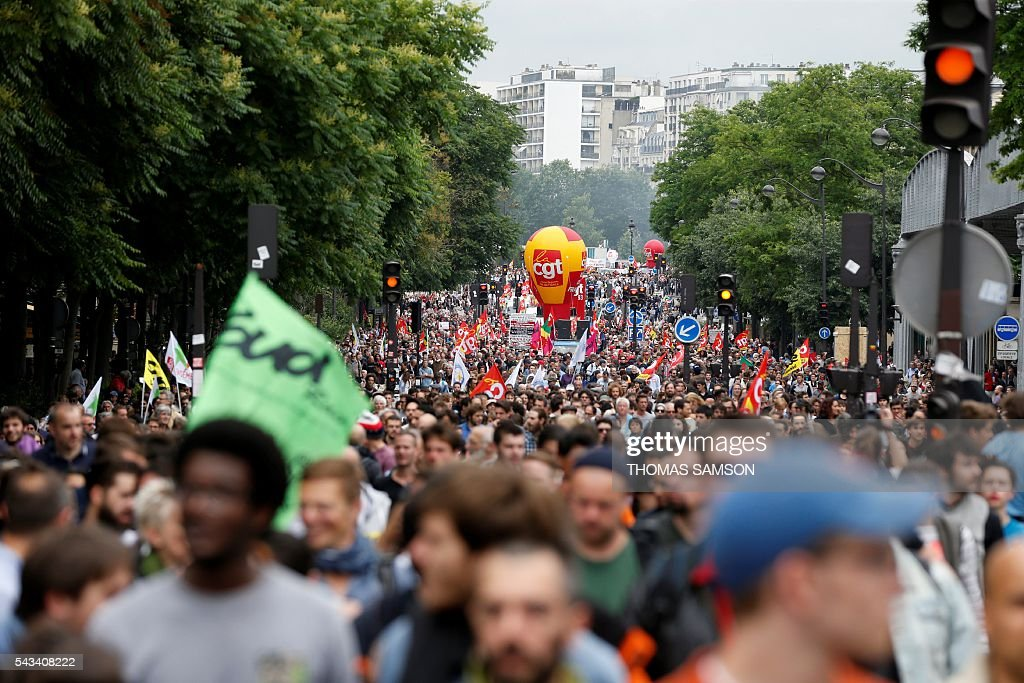 People march during a demonstration against controversial labour reforms, on June 28, 2016 in Paris. Unions have called repeated strikes and marches in opposition to the law, which seeks to bring down France's intractable 10-percent unemployment rate by making it easier to hire and fire workers. / AFP / Thomas SAMSON