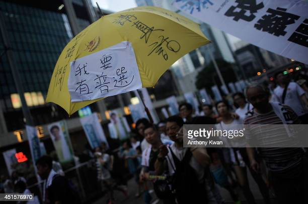 People march on a street during the annual prodemocracy protest on July 1 2014 in Hong Kong July 1 2014 marks the 17th anniversary of Hong Kong's...