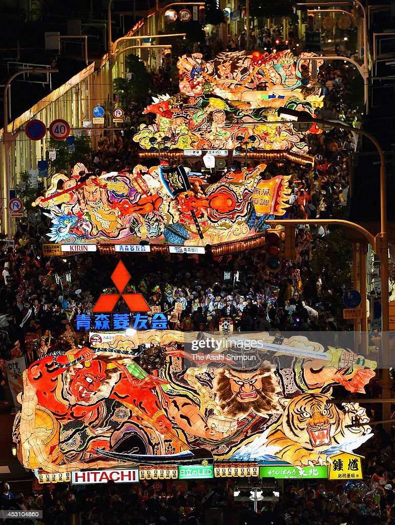 People march on with illuminated 'Nebuta' floats during the Aomori Nebuta Festival on August 2 2014 in Aomori Japan The festival continues until...