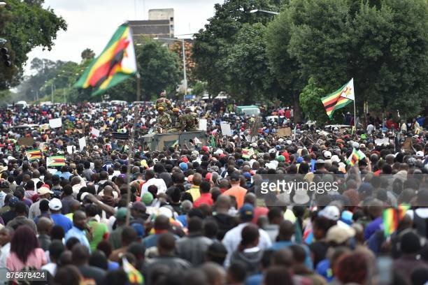 People march past an armoured personnel carrier towards the State House during a demonstration demanding the resignation of Zimbabwe's president on...
