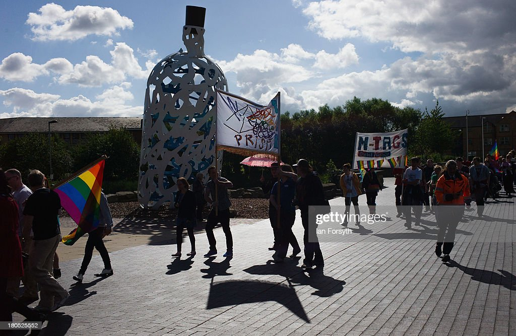 People march past the 'milk bottle' artwork sculpture as they take part in a parade during a Community Pride event on September 14, 2013 in Middlesbrough, England. The parade was the culmination of a three day event to raise awareness and celebrate Lesbian, Gay, Bi-sexual and Transgender life.