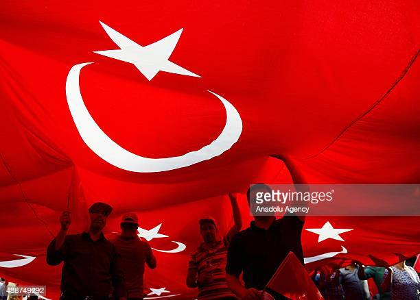 People march under a Turkish flag from the Sihhiye Square through the Grand National Assembly of Turkey to say 'no to terrorism and yes to...