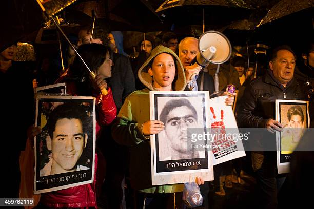 People march with portraits of terror victims during a victims of terror attacks protest of the Palestinian prisoners release on December 30 2013 in...