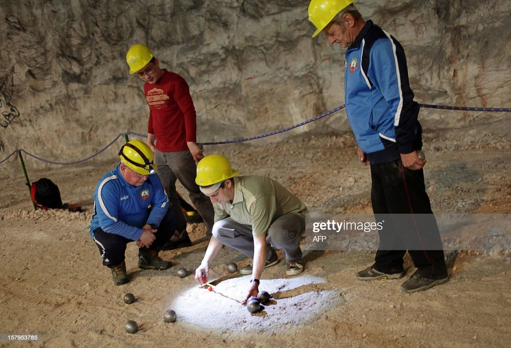 People measure the distance between two balls during a pétanque tournament in the Klodawa Salt Mine, western Poland on December 7, 2012. The tournament is taking place in a special tourist part of the salt mine located 600 meters under ground.