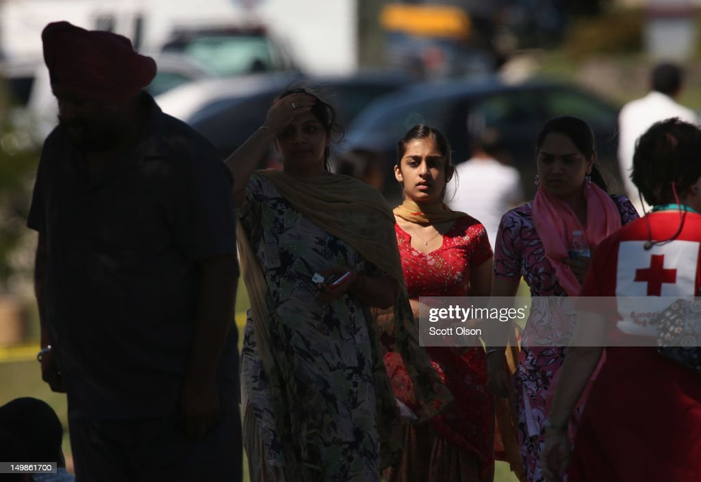 People mill around in front of the Sikh Temple of Wisconsin where at least one gunman fired upon people at a service August, 5, 2012 Oak Creek, Wisconsin. At least six people were killed when a shooter, who was later shot dead by a police officer, opened fire on congregants in the Milwaukee suburb.