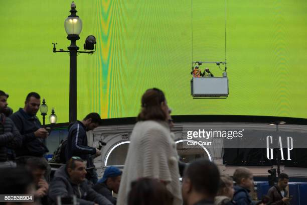 People mill around near the Piccadilly Circus billboard as it displays a test screen on October 18 2017 in London England After nine months of works...