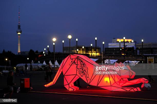 People mill around one of two illuminated tigers in front of the central train station in Berlin August 9 2010 2010 is the year of the tiger and...