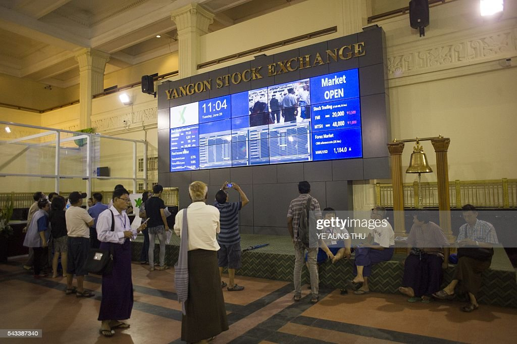 People monitor stock prices and the index displayed on a large video screen at the Yangon Stock Exchange in Yangon on June 28, 2016. / AFP / YE