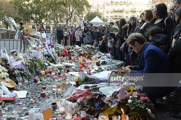 People mourn as they gather at a makeshift memorial near the Bataclan concert hall in Paris on November 15 two days after a series of deadly attacks...