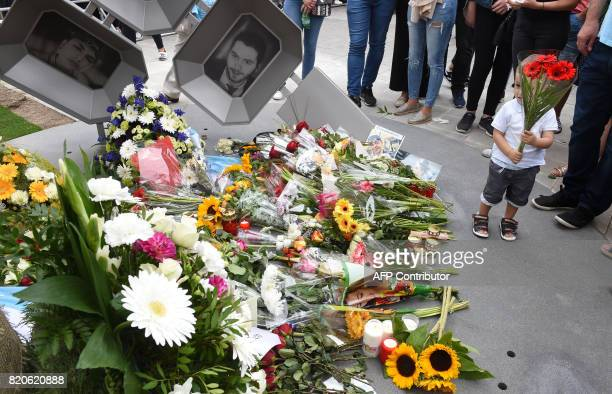 People mourn at a memorial dedicated to the victims of a shooting near the Olympia Einkaufszentrum shopping centre in Munich southern Germany on July...
