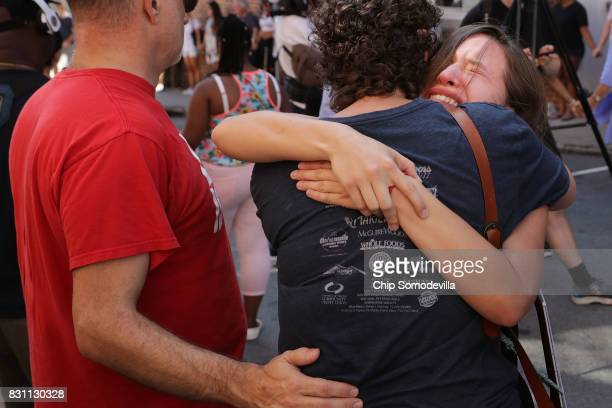 People mourn at an informal memorial where 32yearold Heather Heyer was killed when a car plowed into a crowd of people protesting against the white...