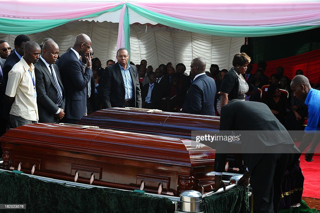 People mourn by the coffins of Mbugua Mwangi and his fiancee Rosemary Wahito in Nairobi on September 27, 2013 after they were both killed in the Westagte Mall attacks. Kenyan and foreign forensics teams scoured the wreckage of a Nairobi shopping mall for bodies and clues after a four-day siege by Islamist gunmen left 67 dead and dozens more missing.