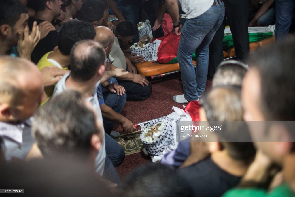 People mourn during the funeral prossesion held for three Palestinians killed during IDF operation at Kalandia refugee camp on August 26, 2013 in Ramallah, West Bank. At least 15 people were injured as Palestinians clash with undercover Israeli troops.