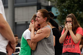 People mourn near the crime scene outside the OEZ shopping center the day after a shooting spree left nine victims dead on July 23 2016 in Munich...