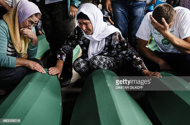 People mourn over coffins of their relatives in Srebrenica on July 9 2015 where 136 bodies found in mass grave sites in eastern Bosnia will be...