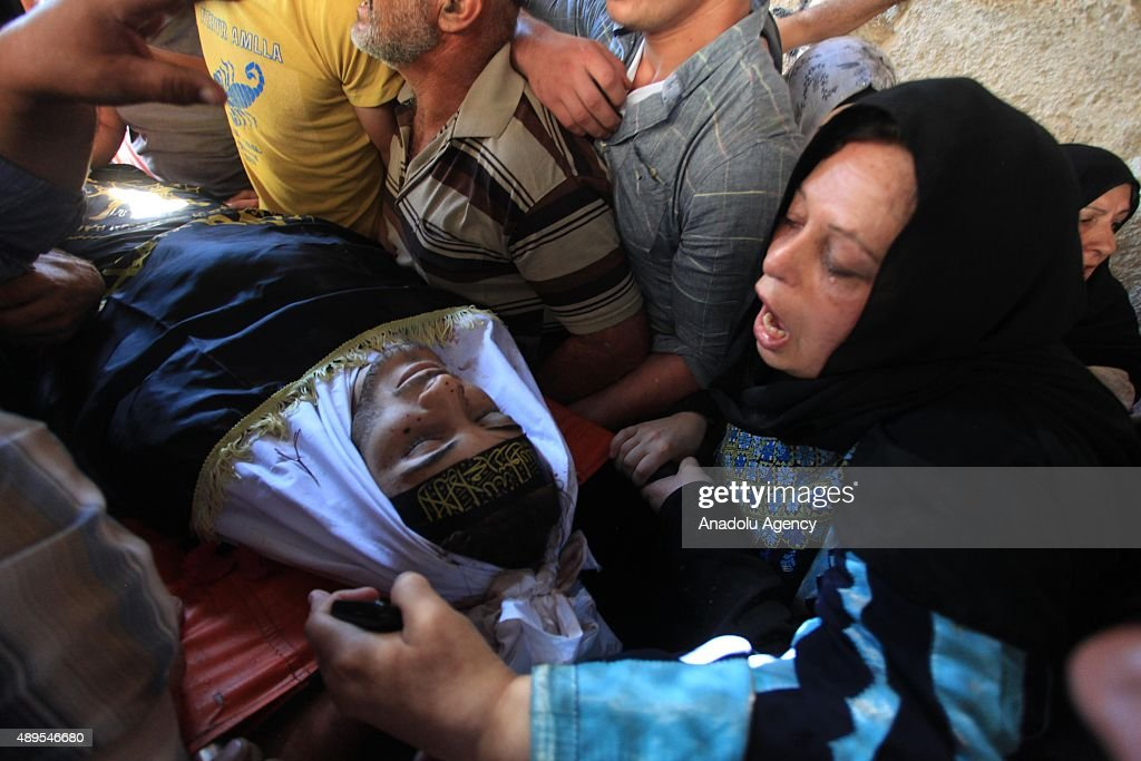 People mourn over the body of Diyaa Abdul Halim Talahmeh 21-year-old who died when a bomb he was trying to throw at Israeli forces blew up near the West Bank city of Hebron on September 22, 2015.