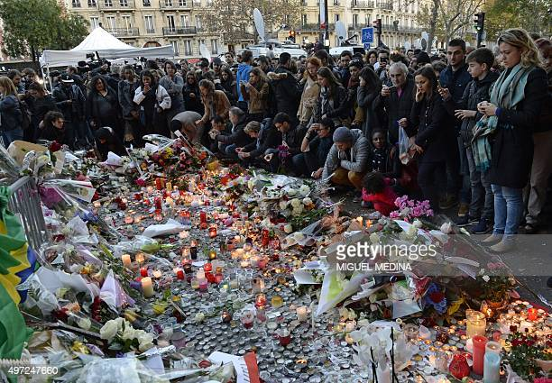 People mourn the dead at a makeshift memorial near the Bataclan concert hall in Paris on November 15 two days after a series of deadly attacks...