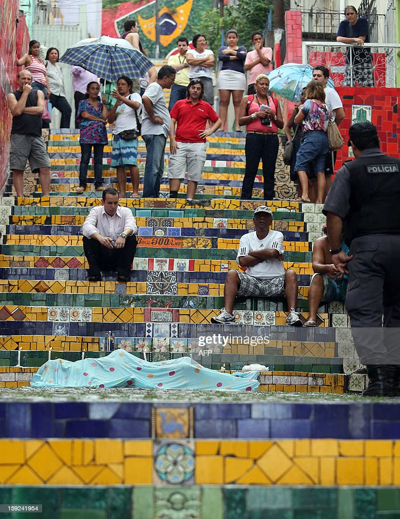 People mourn the remains of Chilean-born artist Jorge Selaron, 65, at 'Selaron Stairs' one of his most famous art works in Rio de Jainero, Brazil on January 10, 2013. The body of Selaron was found in the Rio's historical quarter of Lapa. CESAR