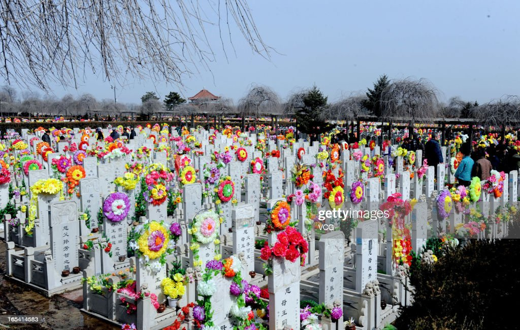 People mourn their deceased family members at a cemetery on April 4, 2013 in Shenyang, Liaoning Province of China. Qingming Festival, also known as the 'Tomb Sweeping Day', which falls on April 4 this year, is a traditional time when people pay their respects to the deceased and ancestors, involving cleaning, repairing of tombs and sacrifice activities.