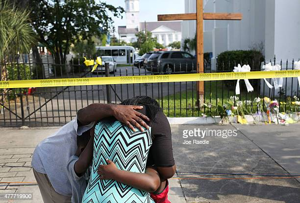 People mourn together in front of the Emanuel African Methodist Episcopal Church after a mass shooting at the church that killed nine people of June...