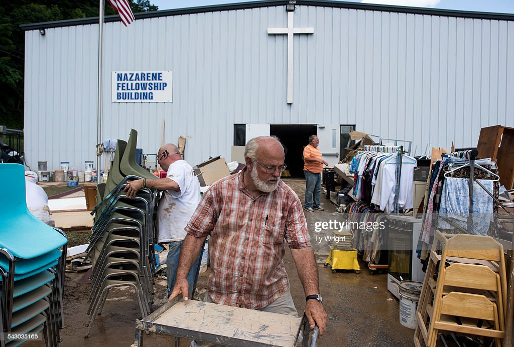 People move piles of water logged debris outside of the Clendenin Church of the Nazarene Community Center on June 25, 2016 in Clendenin, West Virginia. The flooding of the Elk River claimed the lives of at least 23 people in West Virginia.