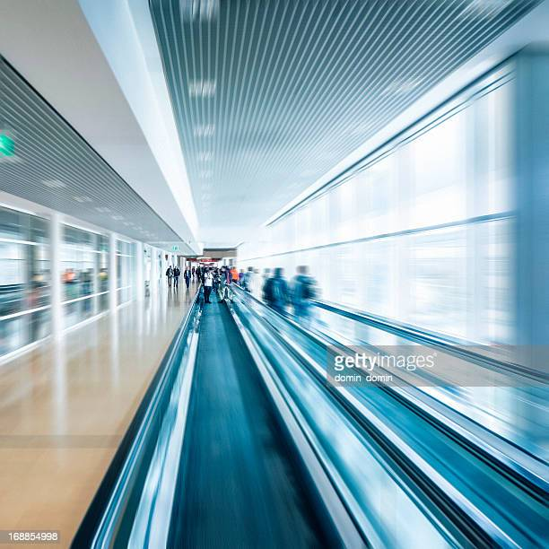 People moving on escalator, walkway in modern office building