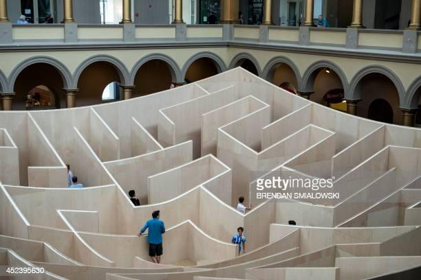People navigate a maze at the National Building Museum July 19 2014 in Washington DC AFP PHOTO/Brendan SMIALOWSKI