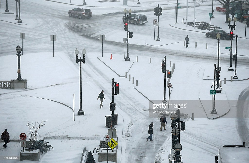 People navigate snow covered streets near Union Station March 3, 2014 in Washington, DC. The Washington area has been hit by repeated snow storms throughout the winter.
