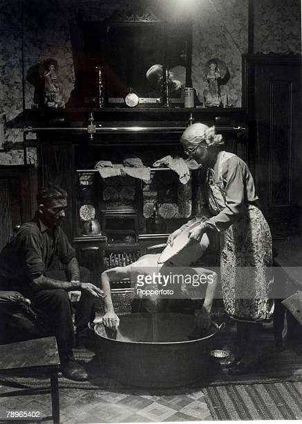 People North East England A miner and his wife wash their sons hair over a tin tub in the lounge infront of the fire