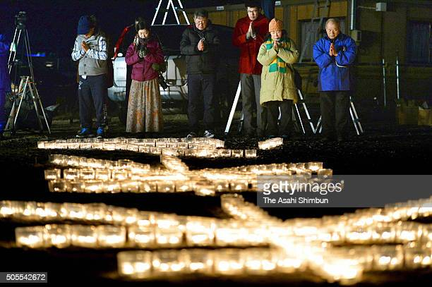 People observe a minute of silence as Japan marks the 21st anniversary of the Great Hanshin Earthquake on January 17 2016 in Ishinomaki Miyagi Japan...