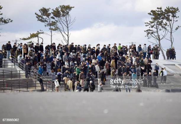 People observe a minute of silence for the victims on a coastal levee on the sixth anniversary of the Great East Japan Earthquake and following...