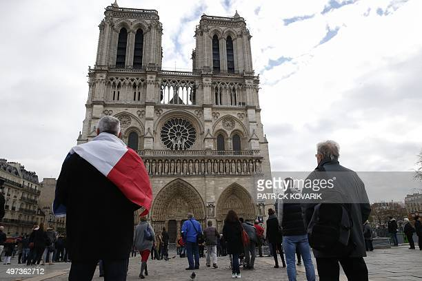 People observe a minute of silence in front of the Nodre Dame Cathedral on November 16 2015 in Paris to pay tribute to victims of the attacks claimed...
