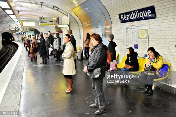 People observe a minute of silence on November 16 2015 at Republique subway station in Paris to pay tribute to victims of the attacks claimed by...