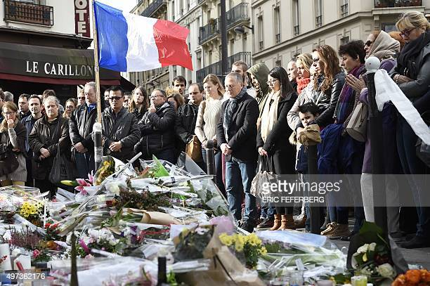 People observe a minute of silence on November 16 2015 at the Le Carillon cafe at the corner of Rue Bichat and Alibert in the 10th arrondissement and...