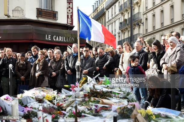 People observe a minute of silence on November 16 2015 at the Le Carillon cafe at the corner of Rue Bichat and Alibert in the 10th arrondissement in...