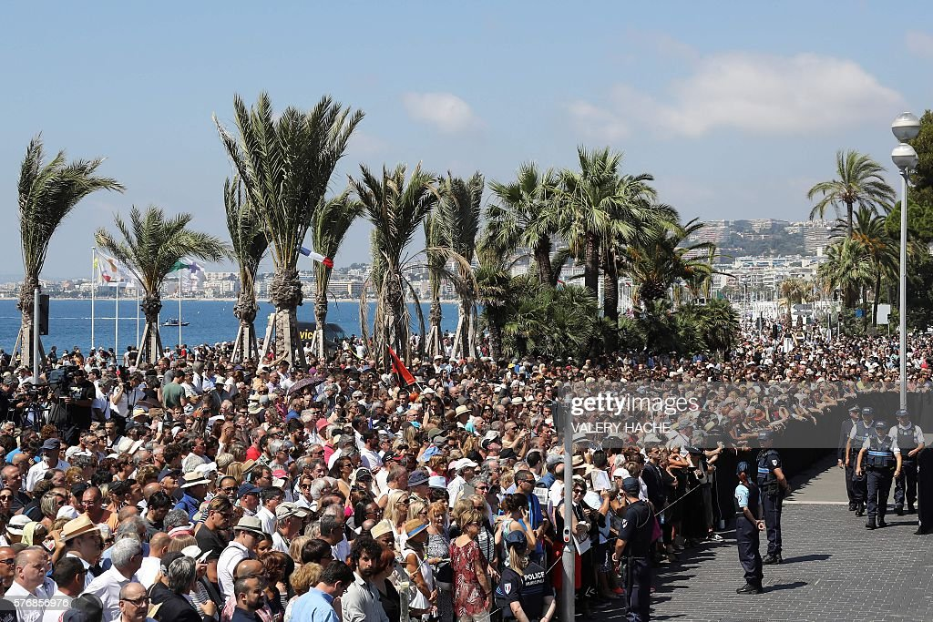 People observe a minute silence on the Promenade des Anglais in Nice on July 18, 2016, in tribute to victims of the deadly Nice attack on Bastille day. France fell silent on July 18, 2016, for the victims of the Nice truck attack, but the mourning was overshadowed by politicians tearing into each other over the massacre. A sea of people thronged the Nice promenade for the emotional minute's silence just days after a Tunisian attacker drove a truck into a crowd at the same place on Bastille Day, killing 84 people and injuring around 300. / AFP / Valery HACHE