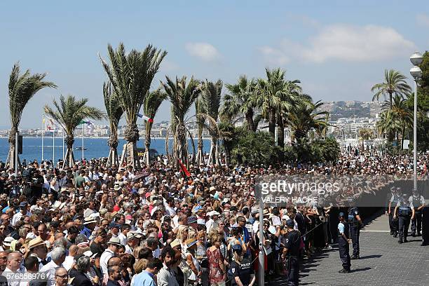 People observe a minute silence on the Promenade des Anglais in Nice on July 18 in tribute to victims of the deadly Nice attack on Bastille day...