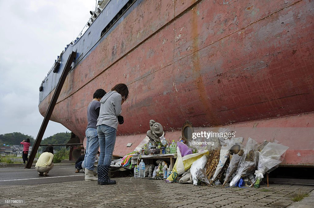 People observe a moment of silence in front of a vessel swept inland by the tsunami which followed the March 11, 2011 earthquake in Kesennuma City, Miyagi Prefecture, Japan, on Thursday, Sept. 6, 2012. Japan's economy expanded in the second quarter at half the pace the government initially estimated, underscoring the risk of a contraction as Europe's debt crisis caps exports. Photographer: Akio Kon/Bloomberg via Getty Images