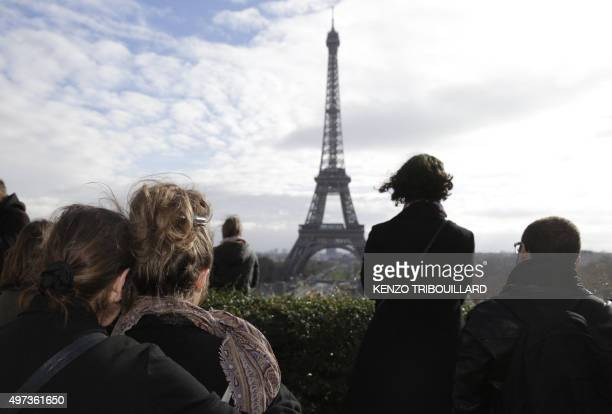 People observe in front of the Eiffel tower a minute of silence at the Place de Trocadero in Paris on November 16 2015 to pay tribute to victims of...