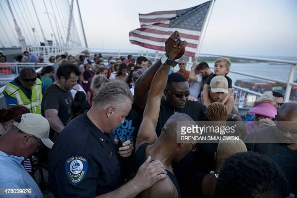 People observe nine minutes of silence on the Arthur Ravenel Jr Bridge June 21 2015 in Charleston South Carolina People crossed the Bridge from Mount...