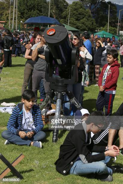 People observe the partial solar eclipse with a telescope at Ciudad Montes Park in Bogota Colombia on August 21 2017
