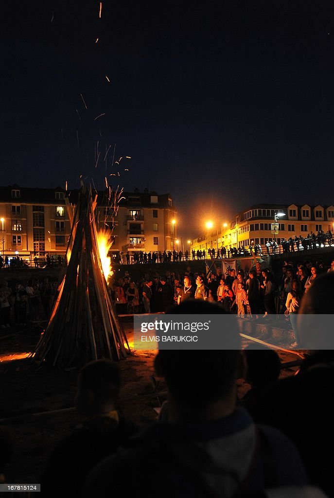 People observe the traditional May 1st camp fire, made in Sarajevo's western suburb of Ilidza, late on April 30, 2013, marking the beginning of celebrations of The International Labour Day.