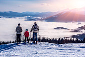 Family of three people stays in front of scenic landscape. These are skiers, they dressed in winter sport jackets and have skies attached