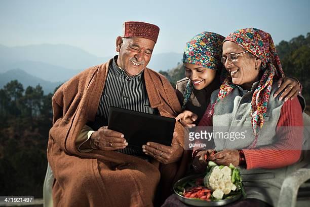 People of Himachal Pradesh: Senior man using laptop with family.
