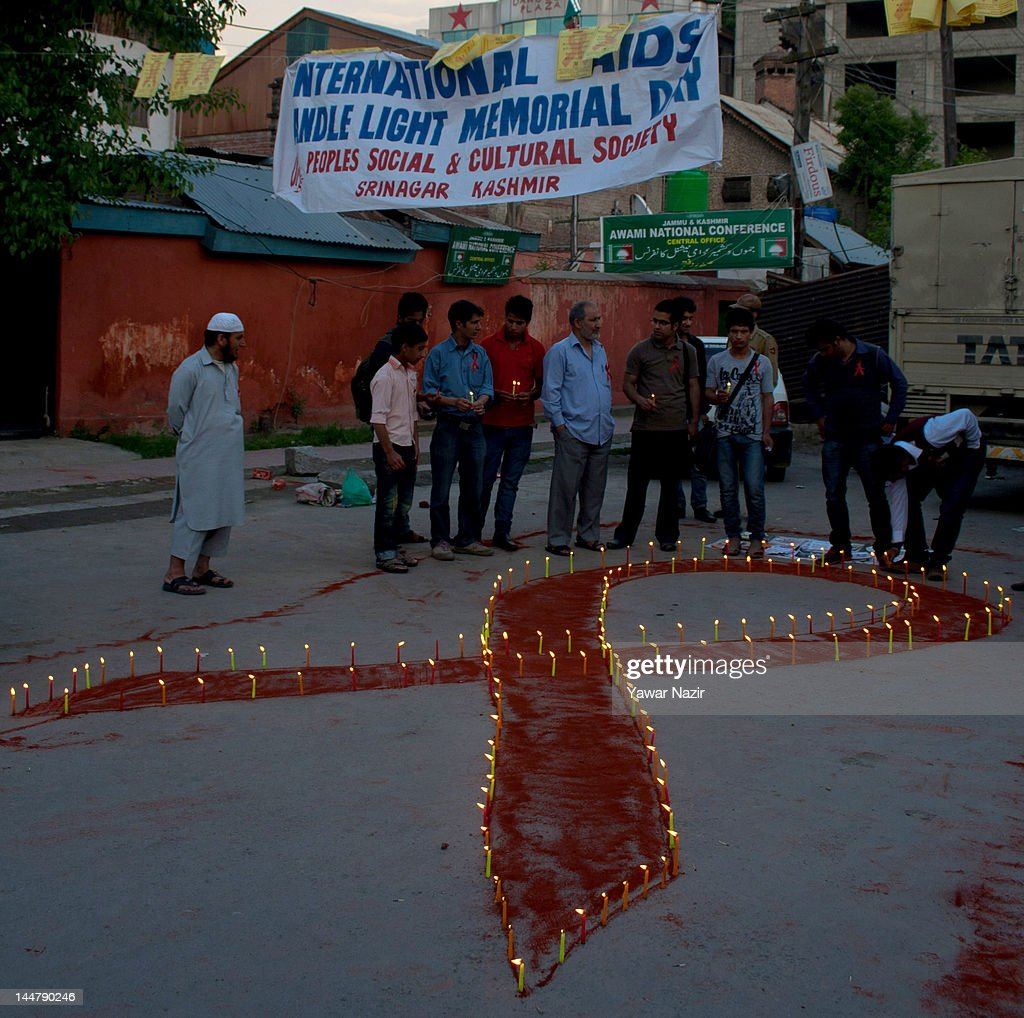 People of Kashmir stand behind a symbolic red ribbon during a candlelight vigil on May 19, 2012 in Srinagar, the summer capital of Indian Administered Kashmir, India. A candle light vigil was organized to commemorate the International AIDS Candlelight Memorial Day for HIV awareness.