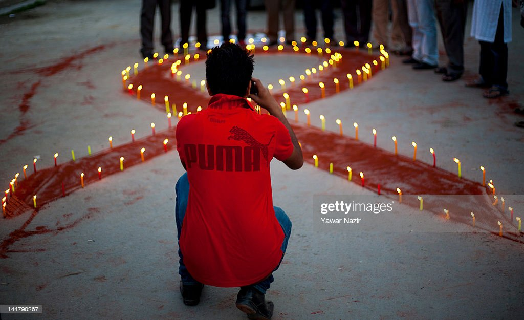 People of Kashmir takes pictures of a symbolic red ribbon during a candlelight vigil on May 19, 2012 in Srinagar, the summer capital of Indian Administered Kashmir, India. A candle light vigil was organized to commemorate the International AIDS Candlelight Memorial Day for HIV awareness.