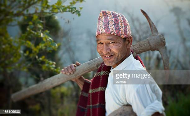 People of Nepal: Happy manual worker with pickaxe and container.
