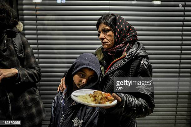 People of the roma community who were evicted from their camp receive food before sleeping on April 3 2013 in front of Lyon's administrative court...