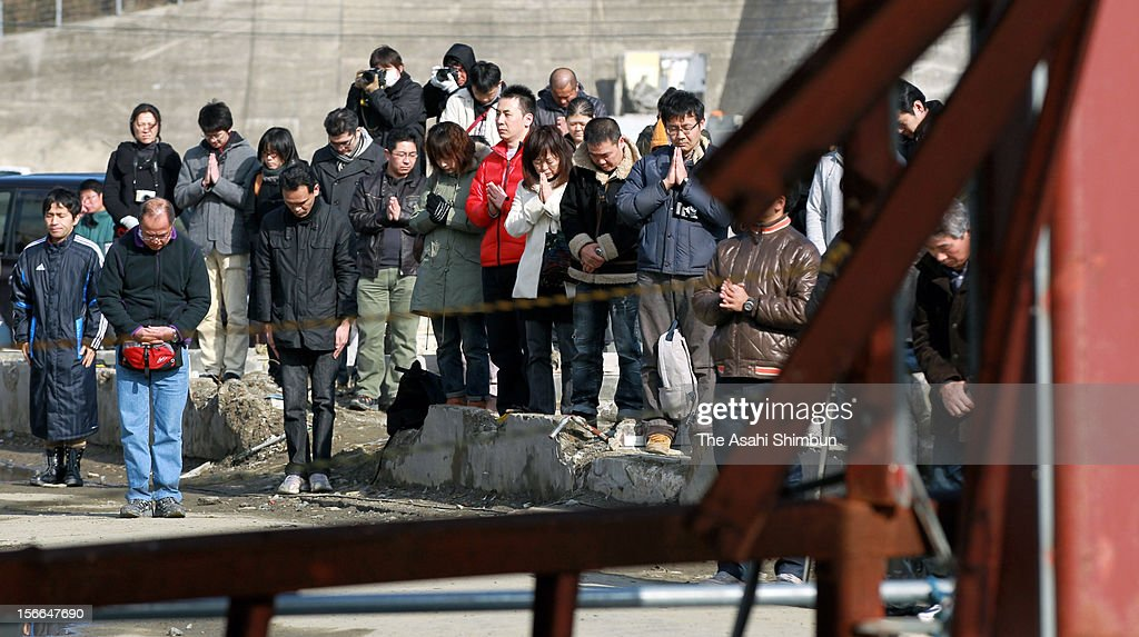 People offer a silent prayer in front of the Minamisanriku Disaster Prevention Center on March 11, 2012 in Minamisanriku, Miyagi, Japan. Japan marks the first anniversary of the Great East Japan Earthquake.