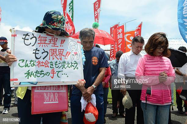 People offer a silent prayer in front of the US Kadena Air Base in Cyatan Okinawa prefecture to protest against the US military presence in Okinawa...